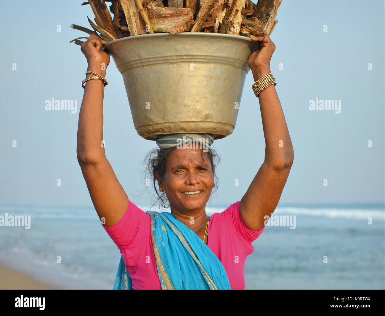 Elderly Orissan woman from the local fishing community at Puri, carrying a heavy load of firewood on her head. - Stock Image
