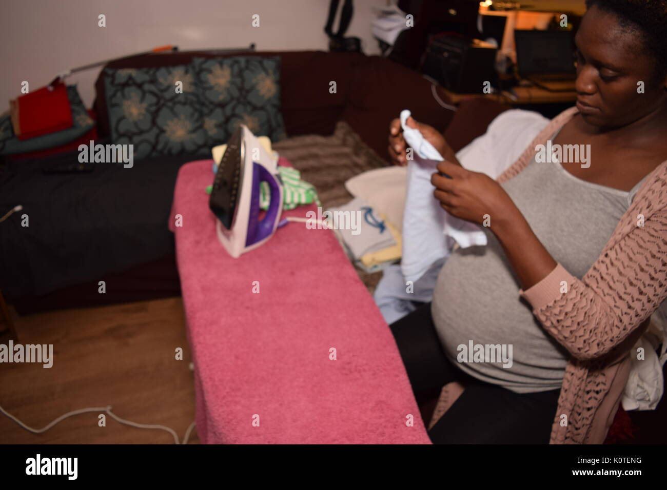 Pregnant woman ironing clothes - Stock Image