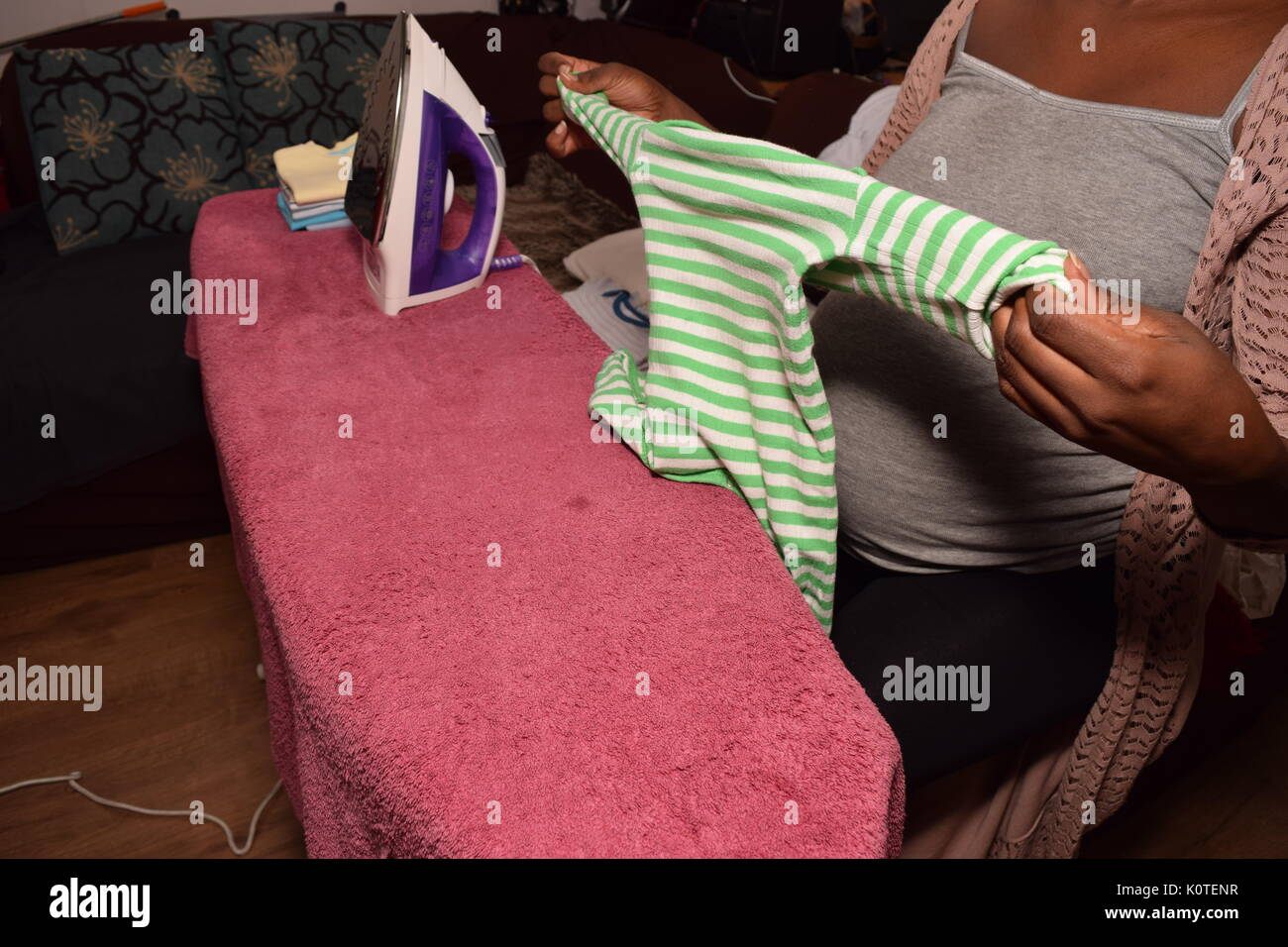Pregnant female ironing clothes - Stock Image