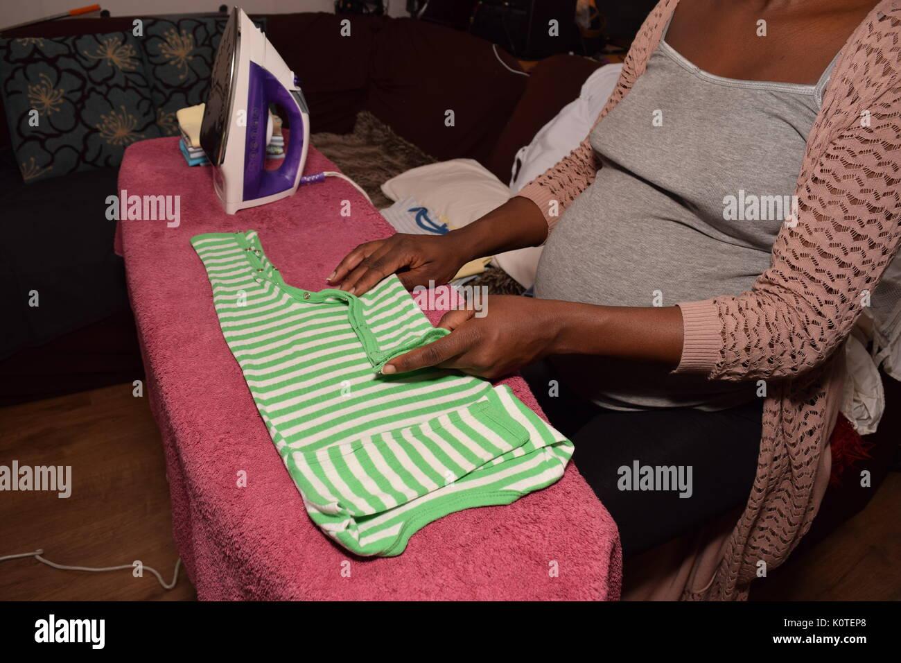 Pregnant female ironing - Stock Image
