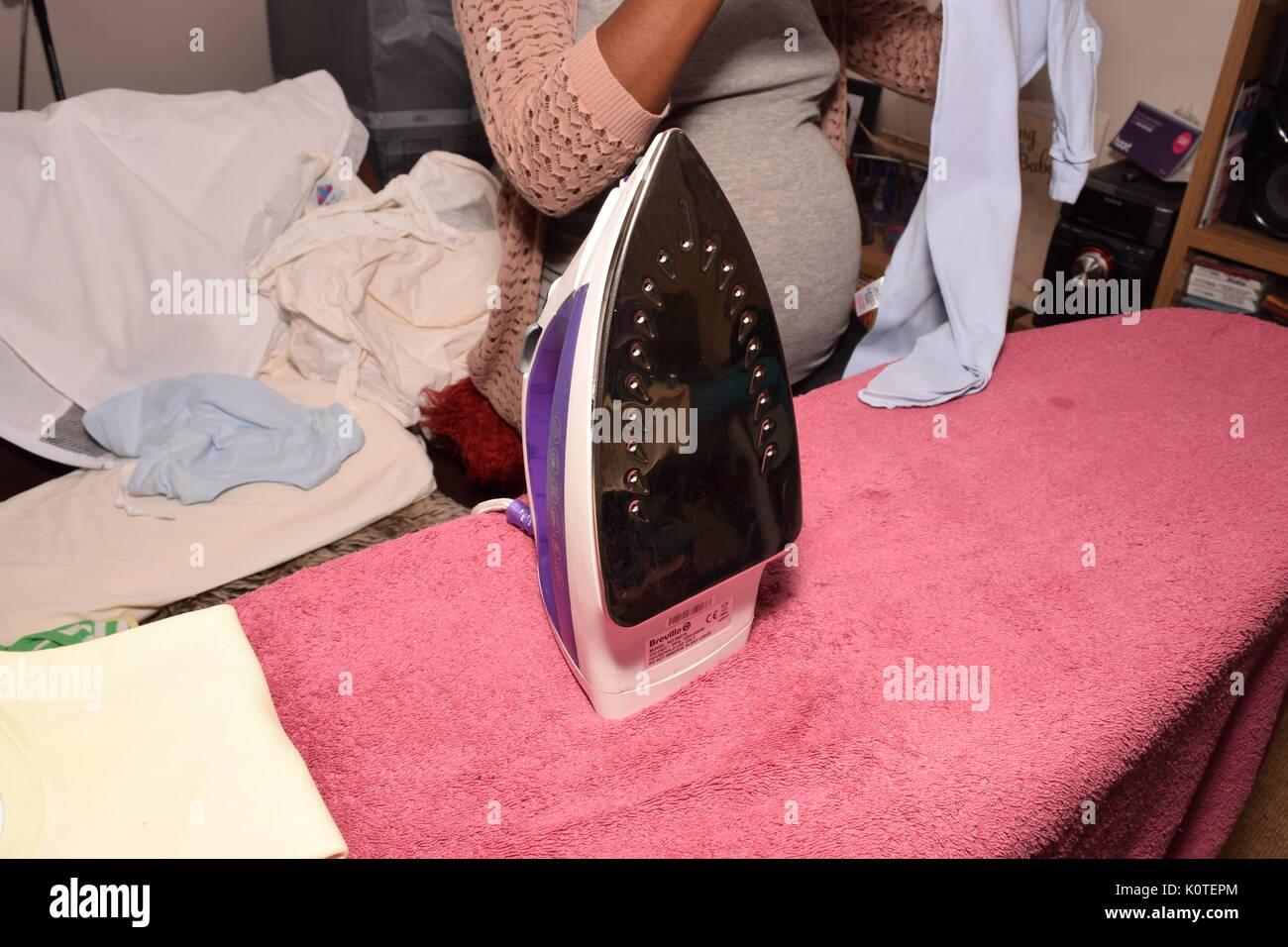 Pregnant woman ironing - Stock Image