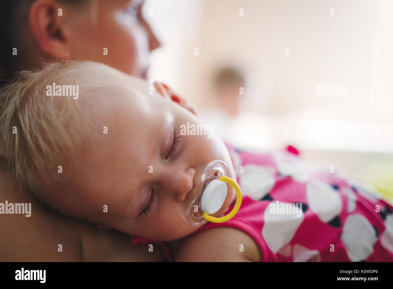 Young mother holding her sleeping newborn baby - Stock Image