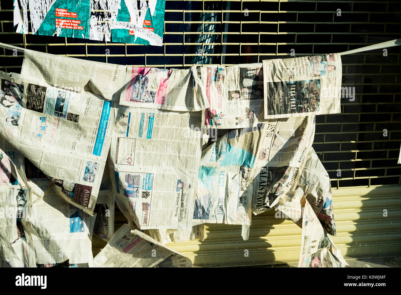 Newspapers hung on a line as if to dry or to hide something within the window in a shop window in East London - Stock Image