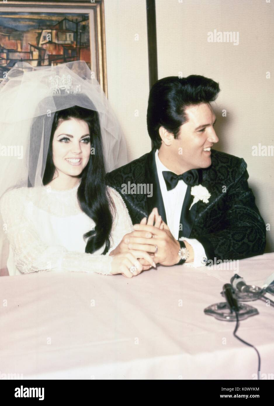 Elvis Presley and Priscilla Presley wedding photo, wearing tuxedo and wedding dress, smiling and holding hands, - Stock Image