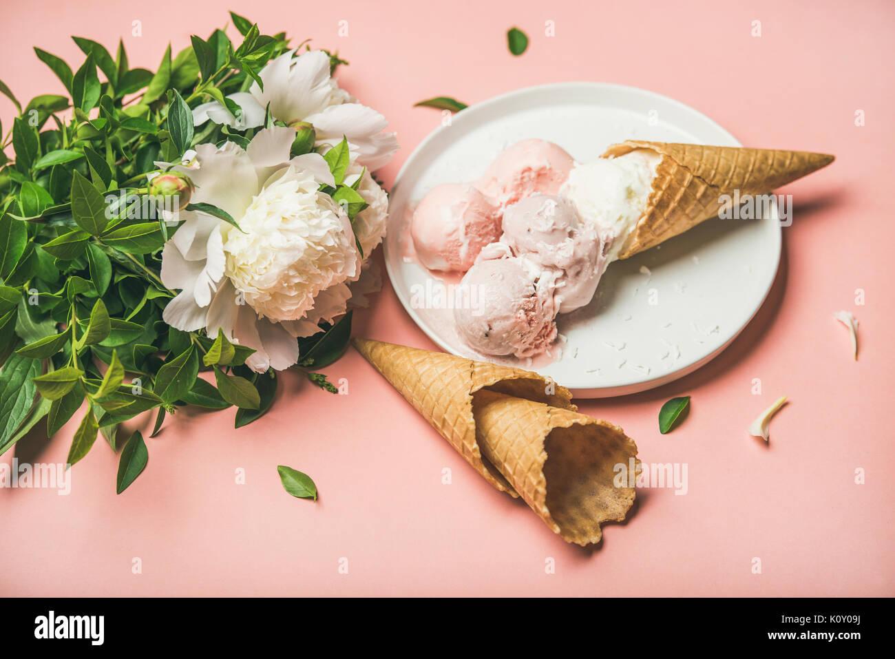 Strawberry and coconut ice cream, cones, white peony flowers - Stock Image