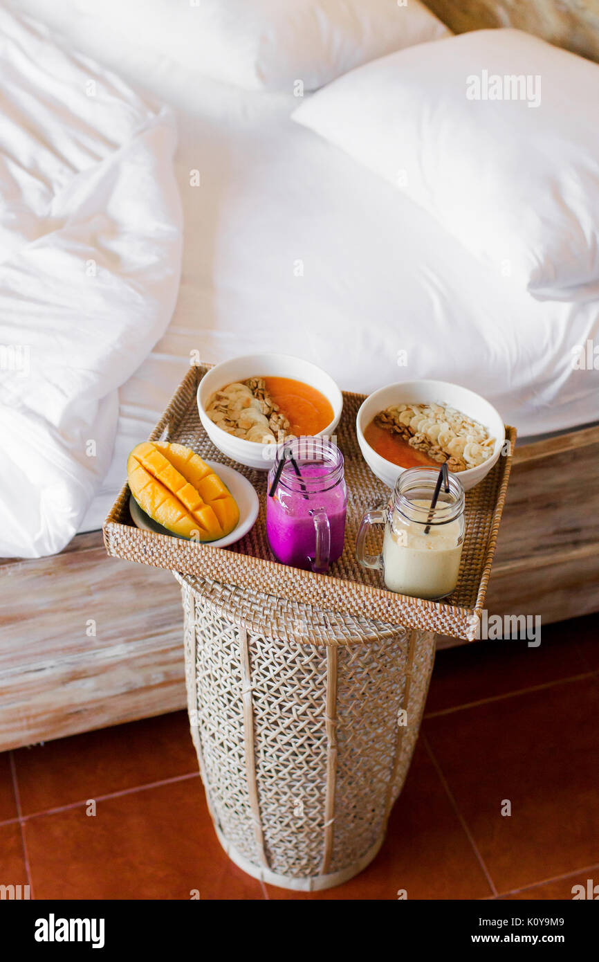 Fresh healthy breakfast in bed for two. Cutted mango, tasty papaya blended smoothie with banana and nuts, tropical - Stock Image