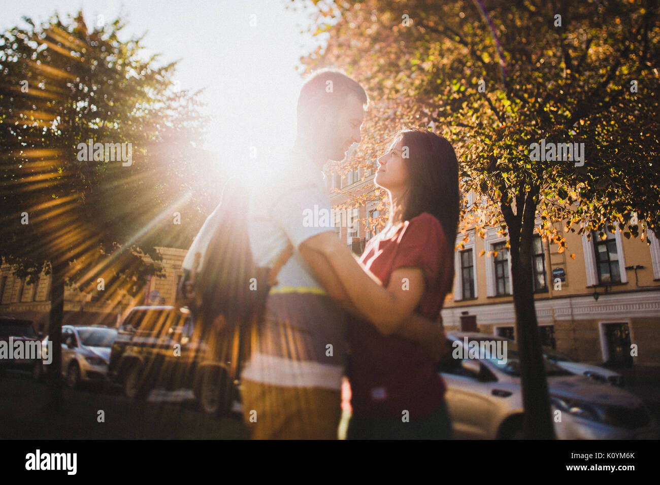 Loving couple tenderly looking at each other in the sun rays closeup - Stock Image