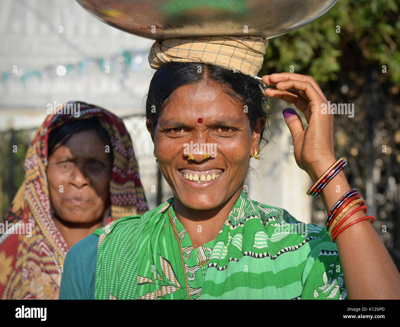 Middle-aged Indian Adivasi woman (Orissan tribal woman) with two distinctive golden nose studs, balancing  on her - Stock Image