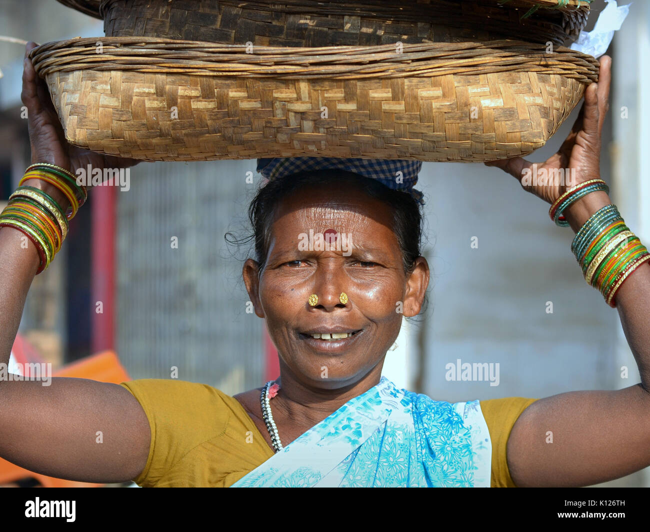 Elderly Indian Adivasi woman (tribal woman) with two distinctive golden nose studs, carrying on her head a set of Stock Photo