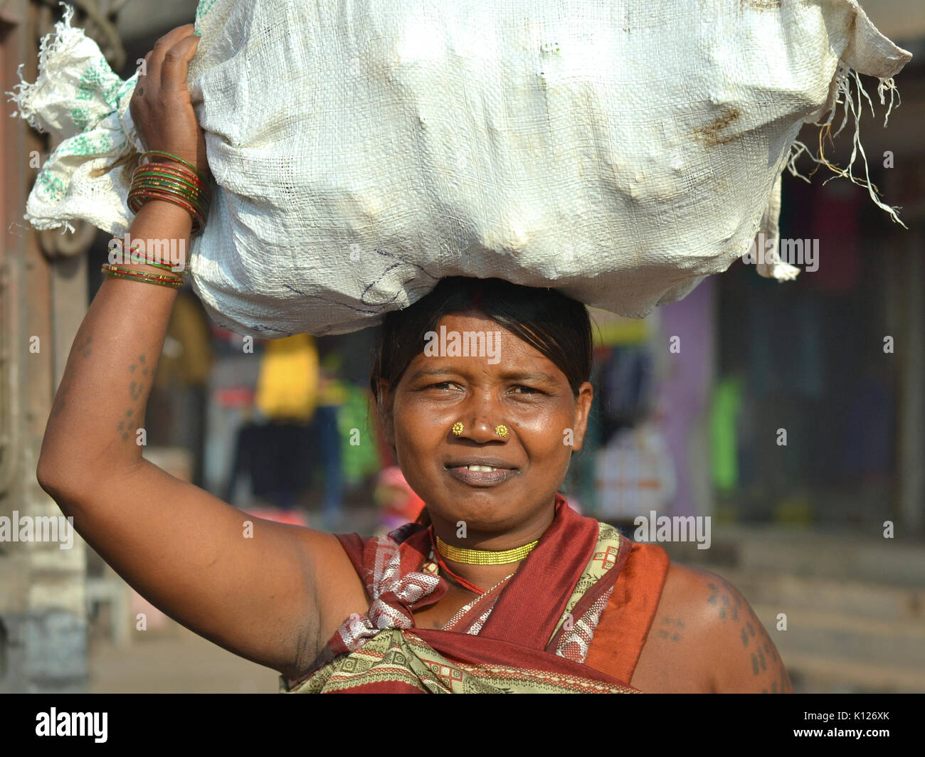 Mature Indian Adivasi woman (tribal woman) with two distinctive golden nose studs, balancing  on her head a heavy Stock Photo