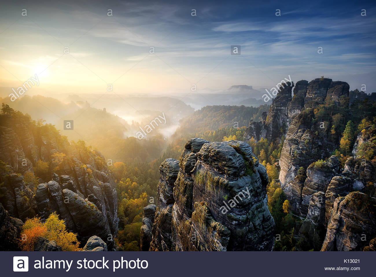 Beautiful panoramic view at sandstone rocks during foggy sunrise at Bastei, Saxon Switzerland, Germany - Stock Image