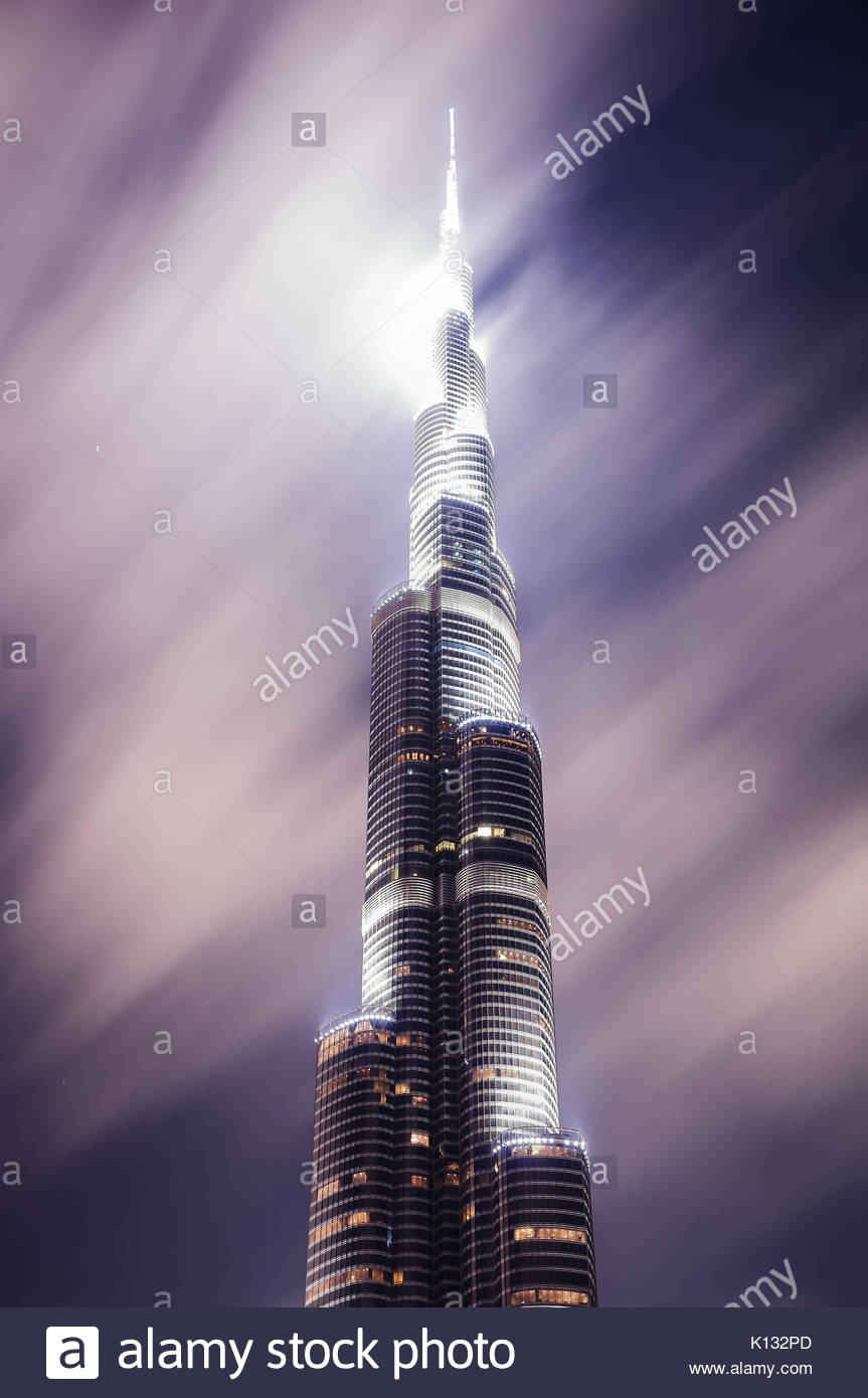 DUBAI, UAE - MAR 23, 2014: Tallest skyscraper of the world called Burj Khalifa during night with motion clouds, - Stock Image