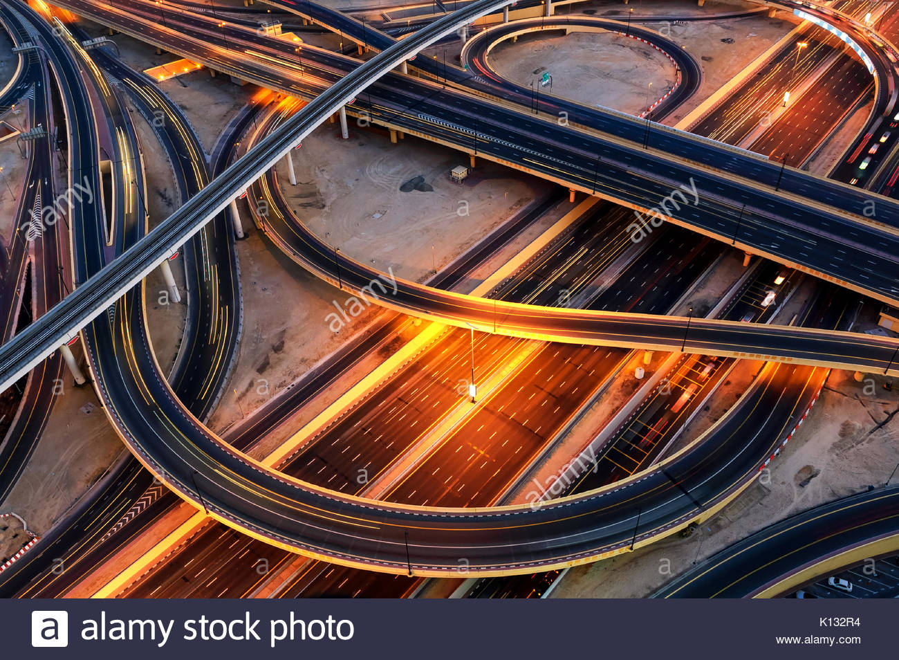 Extraordinary thoroughfare leading to Abu Dhabi during night rush hour near biggest skyscrapers. Traffic jam with - Stock Image