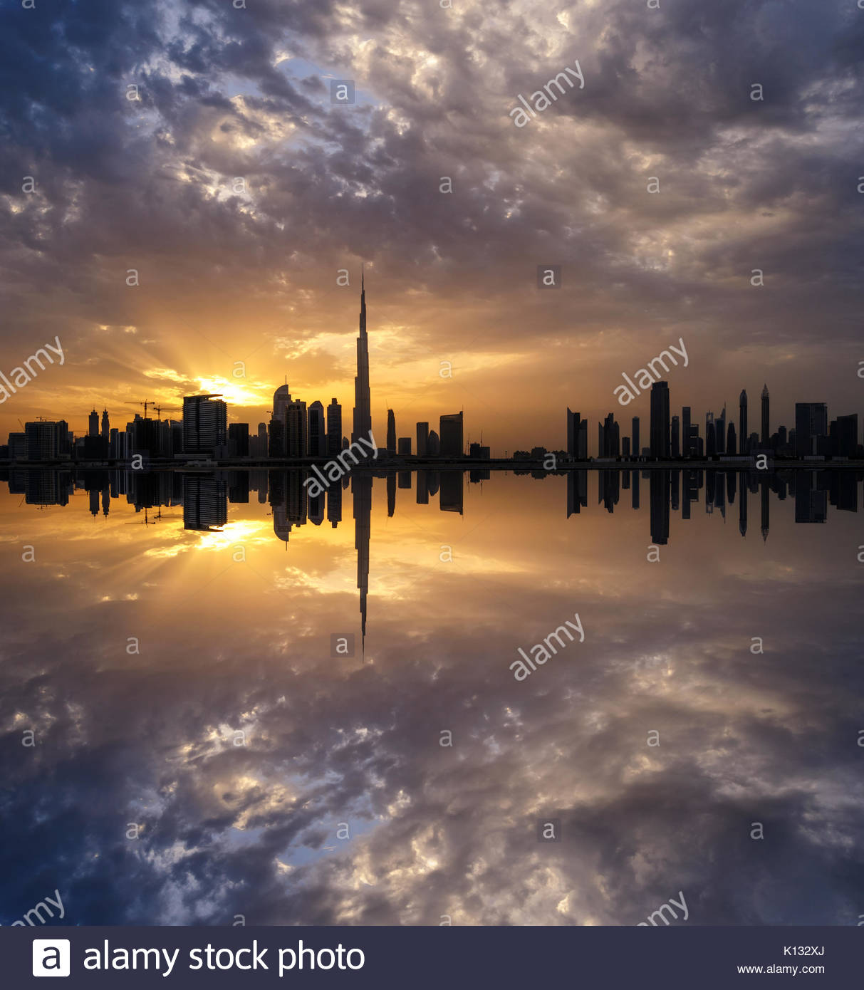 Fascinating reflection of tallest skyscrapers in Business Bay district during dramatic sunset. Downtown summer day. - Stock Image