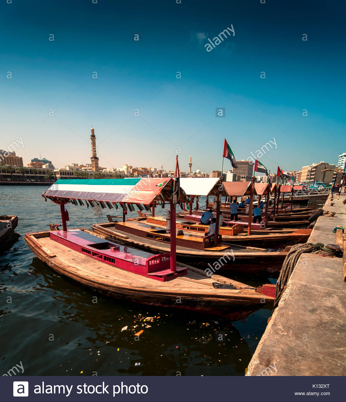 Traditional Abra taxi boats in Dubai creek - Deira during sunny day, Dubai Deira, United Arab Emirates - Stock Image
