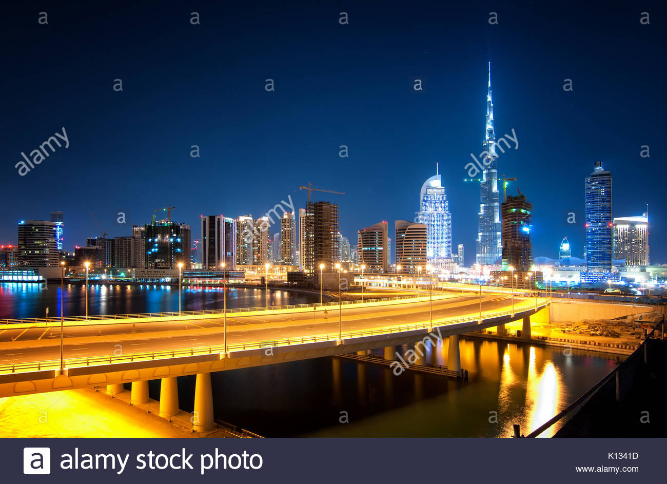 Fascinating reflection of tallest skyscrapers in Business Bay district during calm night with amazing bridge. Downtown - Stock Image