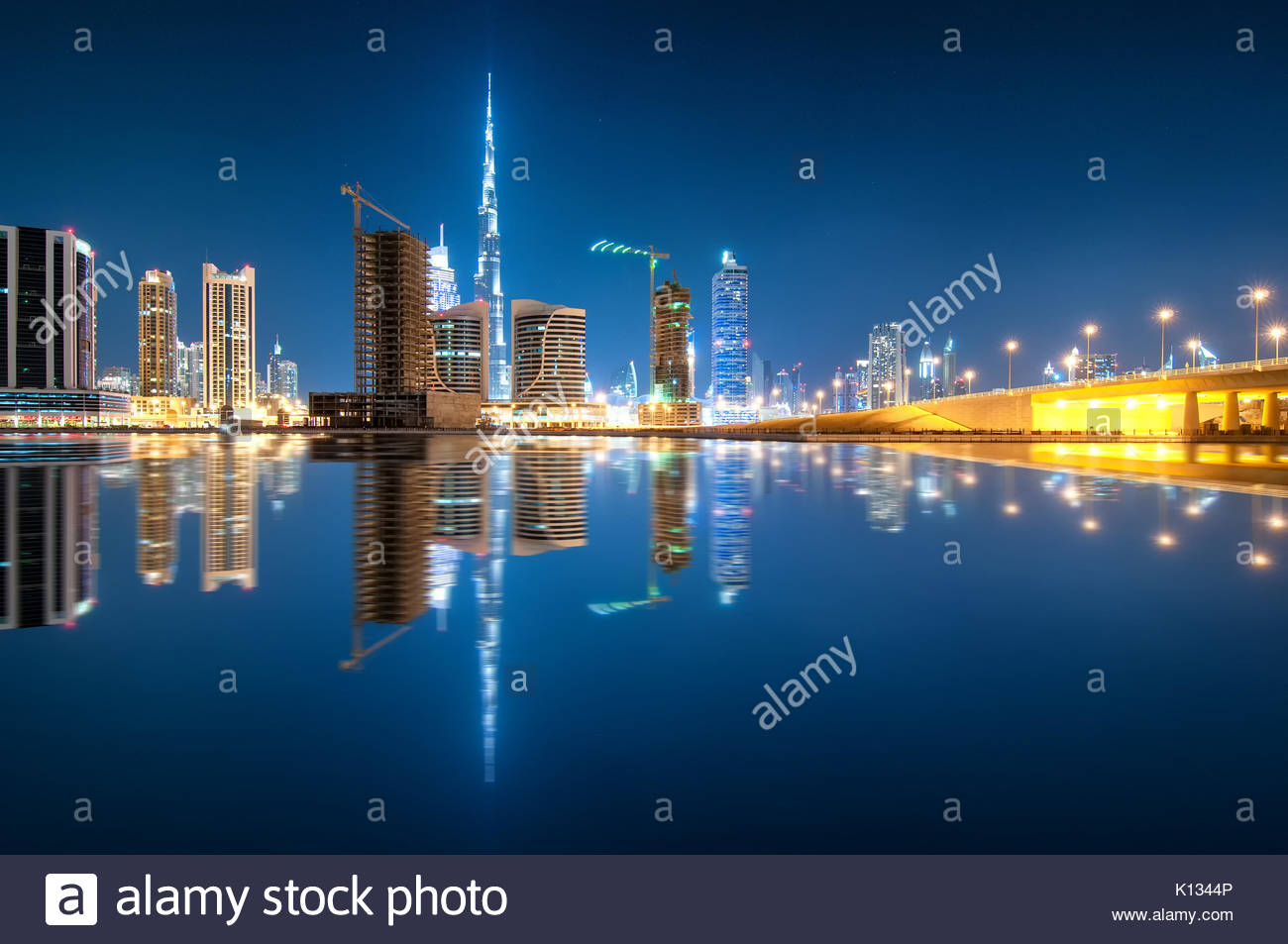 Fascinating reflection of tallest skyscrapers in Business Bay district during calm night. Downtown summer night. - Stock Image