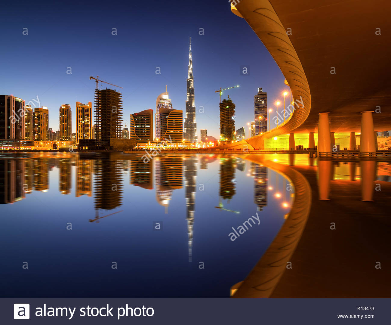 Fascinating reflection of tallest skyscrapers in Business Bay district during colorfull sunset near amazing bridge. - Stock Image