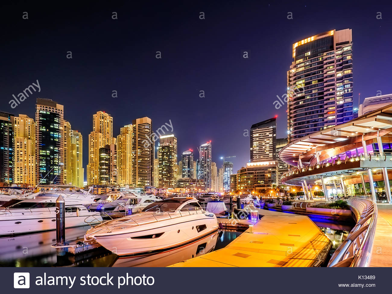 Incredible colorful night dubai marina skyline. Luxury yacht dock. Dubai, United Arab Emirates. - Stock Image