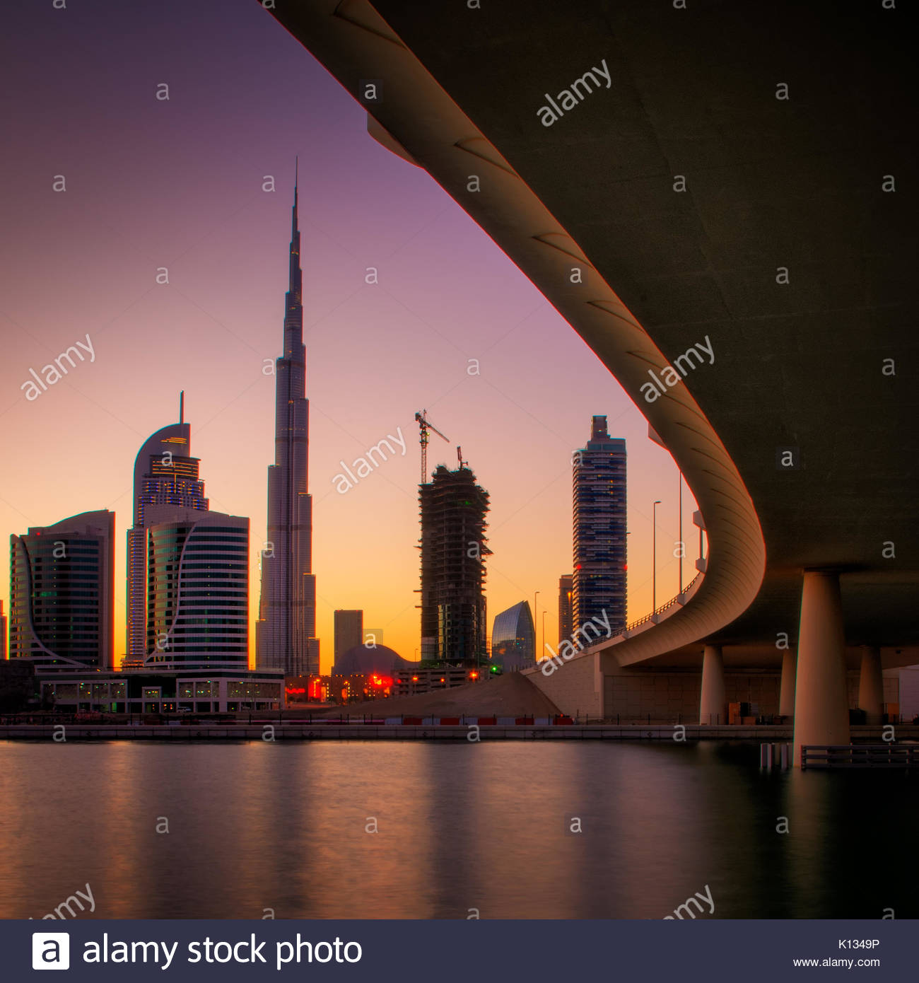 Fascinating reflection of tallest skyscrapers in Business Bay district during colorful sunset near amazing bridge. - Stock Image