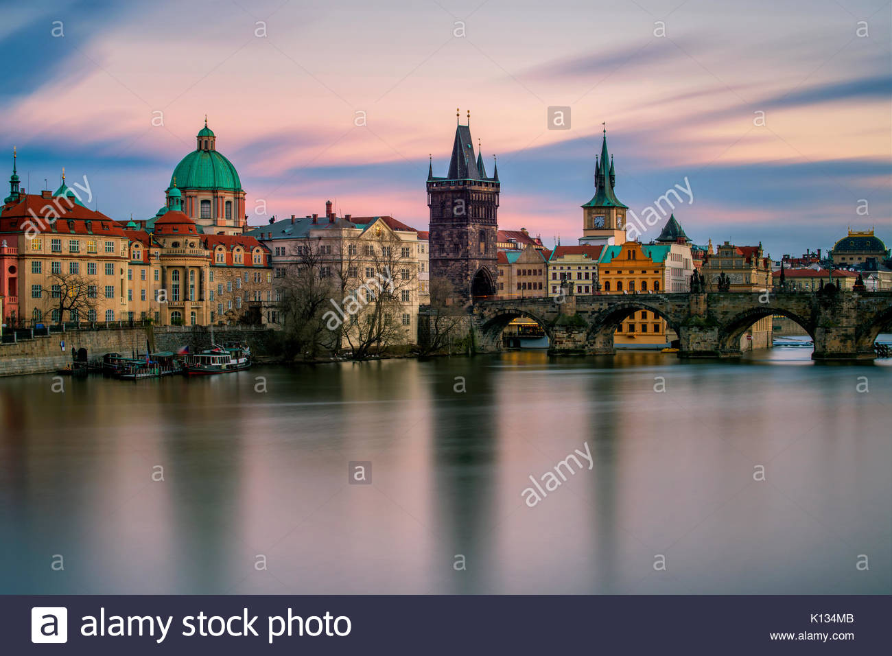 Amazing towers of Charles bridge and old town district with reflection at Vltava river during cloudy sunset, Prague, - Stock Image