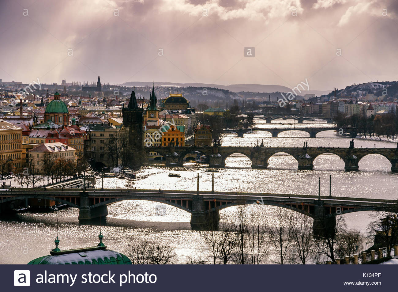 Amazing towers of Charles bridge and old town district with several bridges at Vltava river during winter day. Heavy - Stock Image