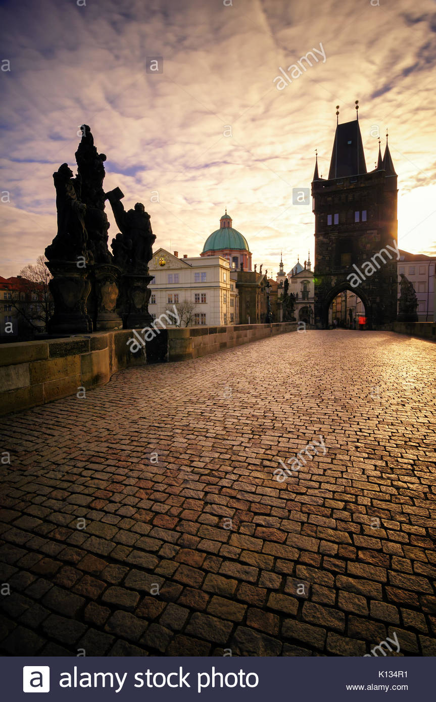 Beautiful sunrise at famous Charles Bridge. Bridge with amazing tower and old statues at early morning. Typical - Stock Image