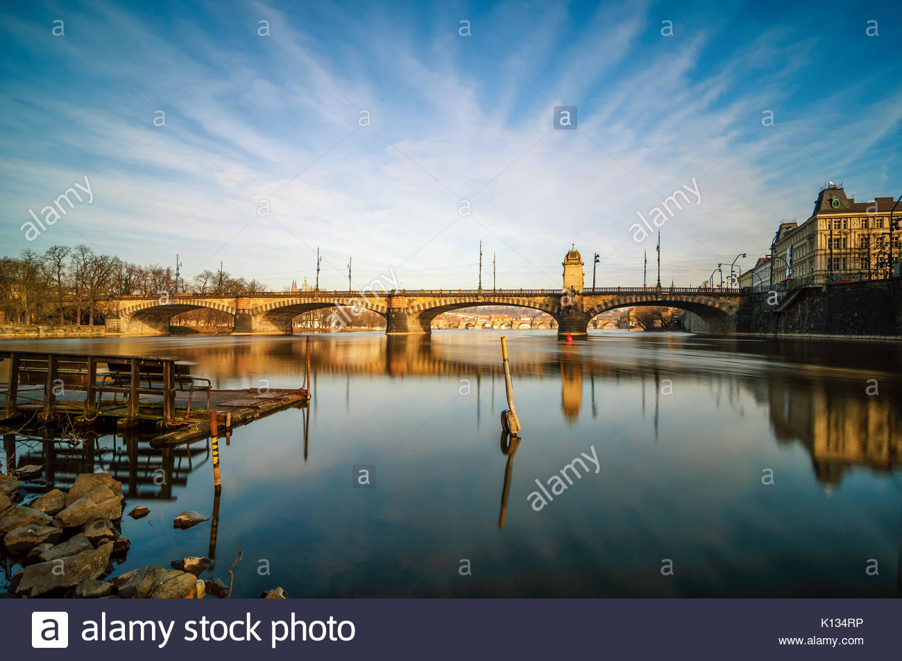 Amazing sunrise view at Vltava river bridge and boat with clear water reflection. Typical Prague sunny morning. - Stock Image