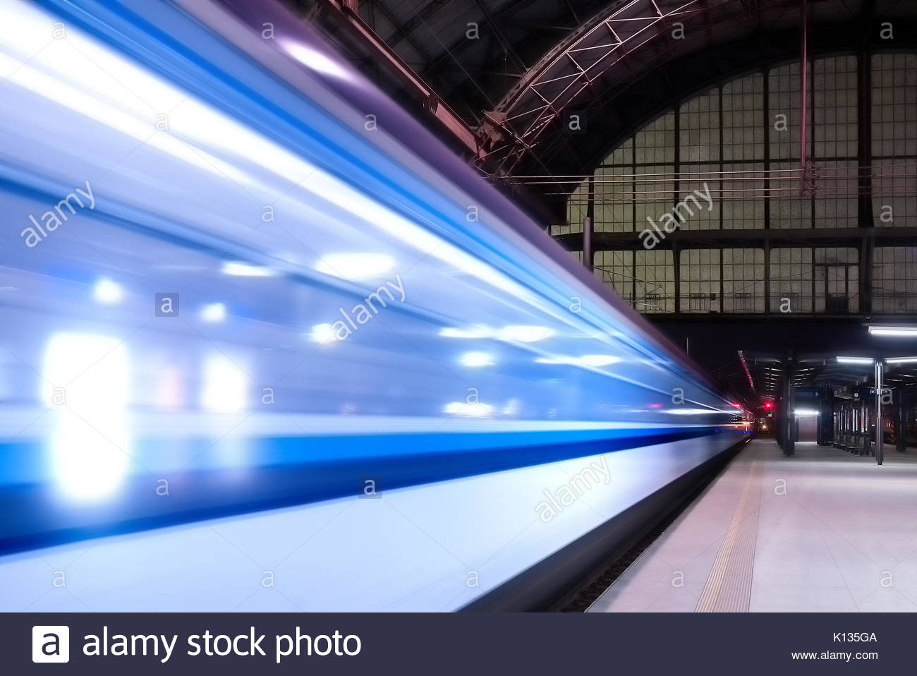 Train speeding through railway station during busy night time with extended motion. - Stock Image