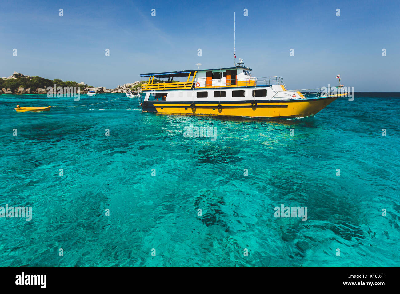 Tourist diving boat near island shore with turquoise clear transparent water. Idyllic view of Similan Islands - Stock Image