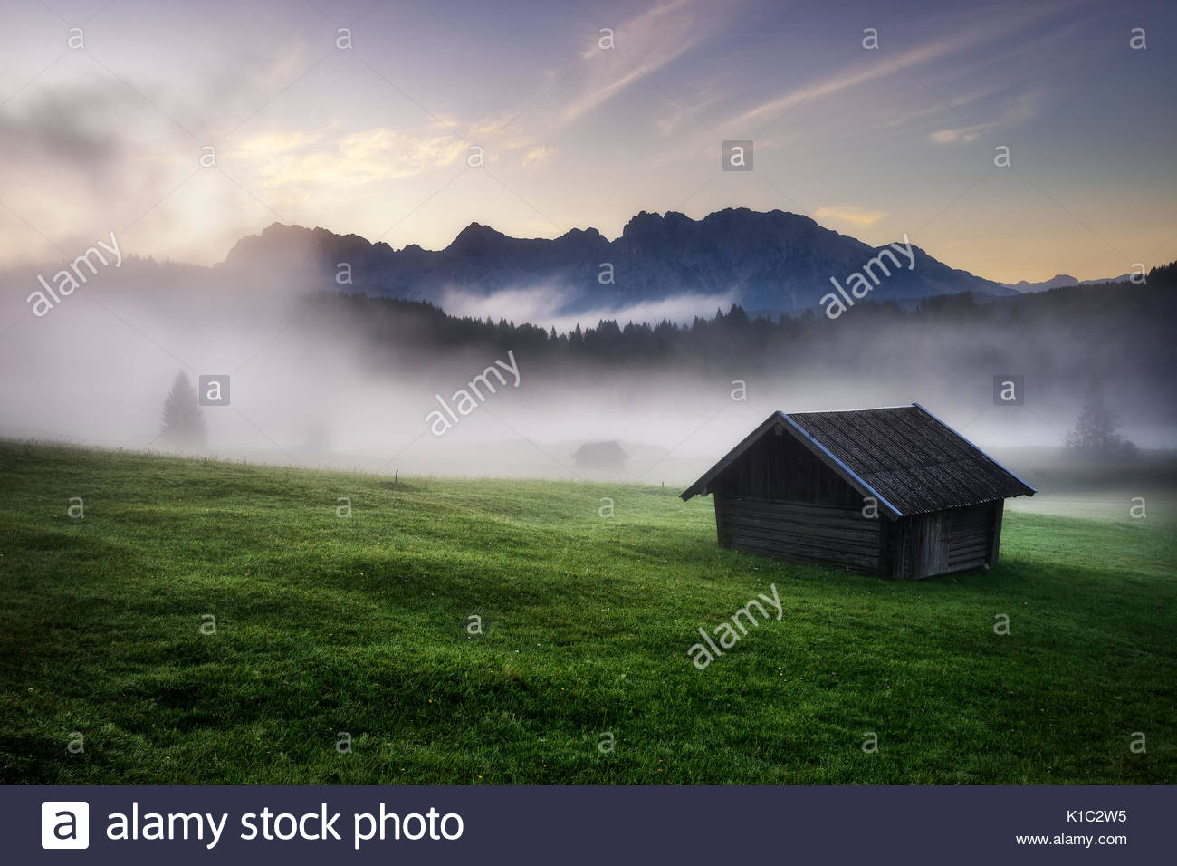 Geroldsee forest during summer day with beautiful foggy sunrise over mountain peaks, Bavarian Alps, Bavaria, Germany. - Stock Image