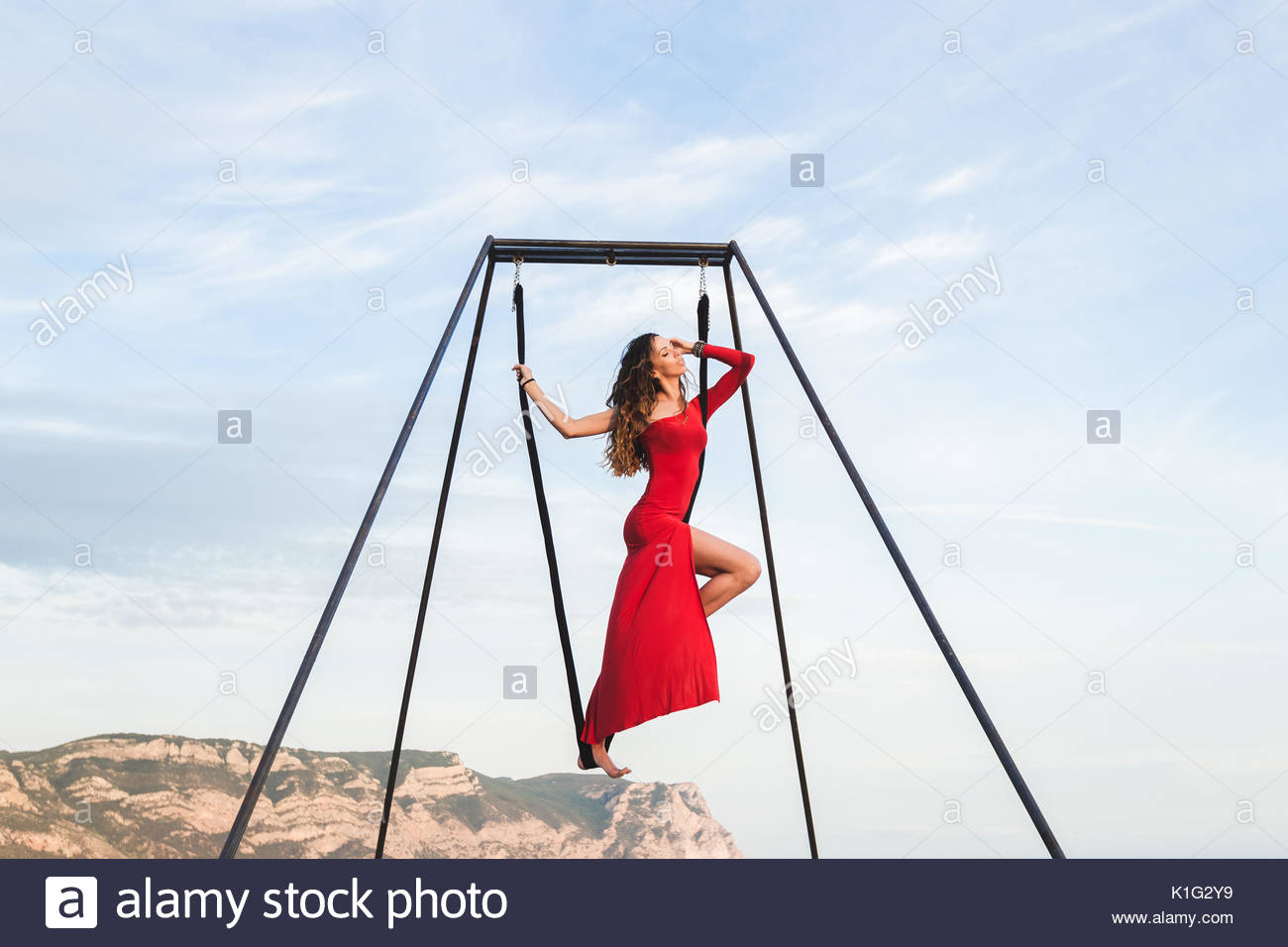 Woman in red dress practicing fly-dance poses in a hammock outdoor with a mountain view - Stock Image