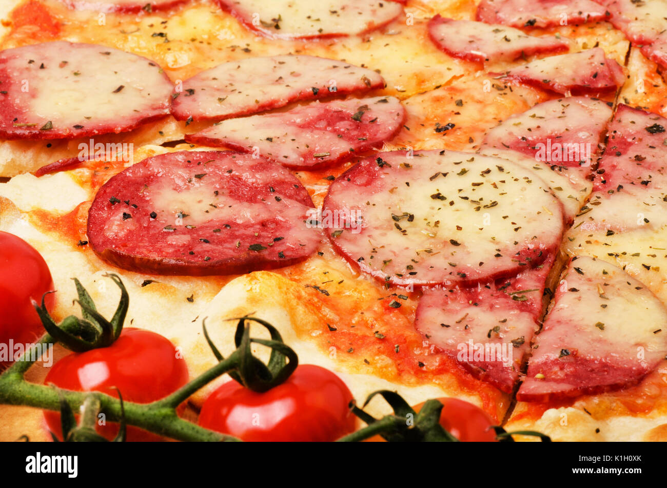 Tasty salami pizza with cherries ingredient close-up - Stock Image