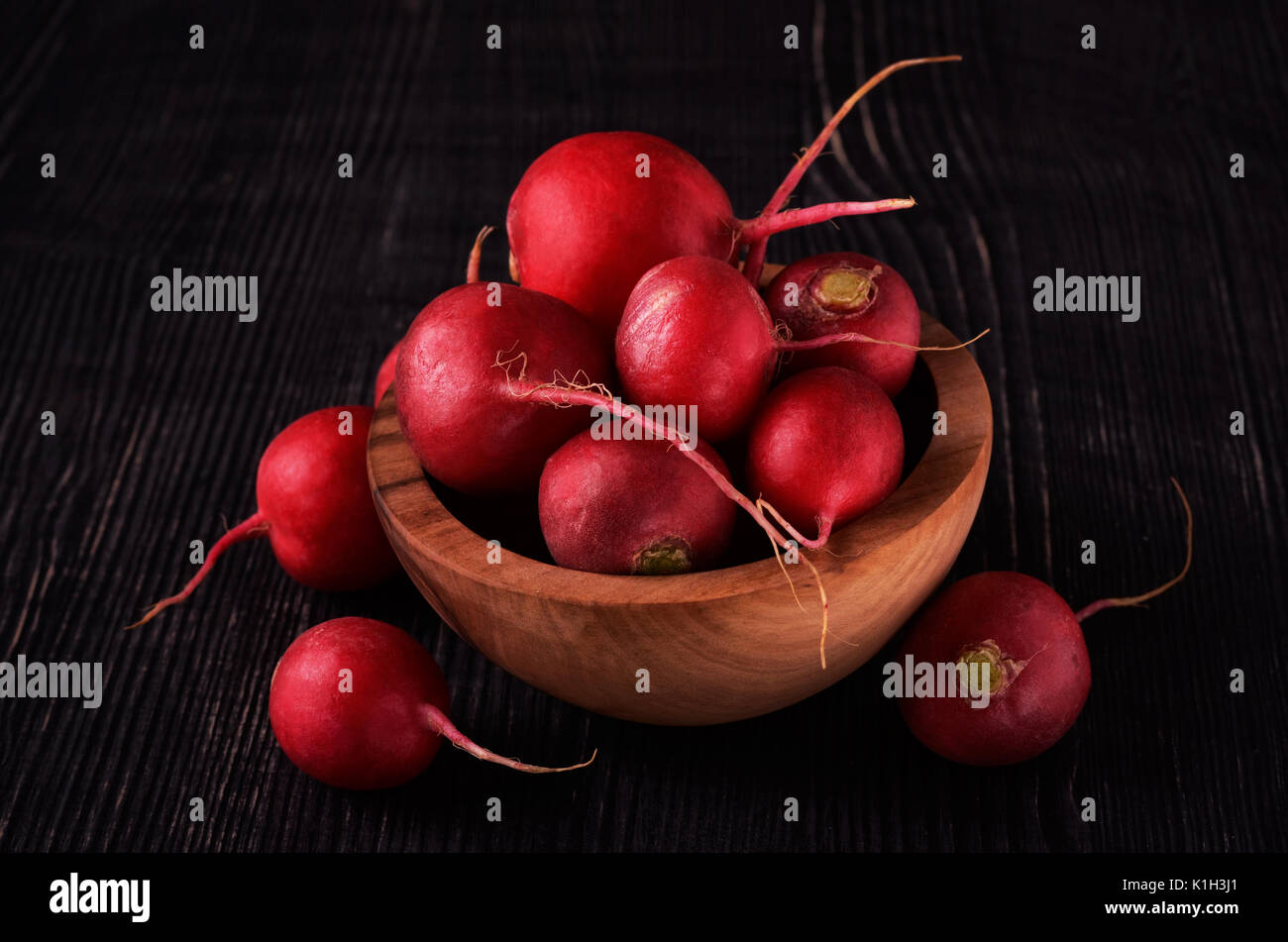 Organic red radish on dark in wood bowl wooden background - Stock Image