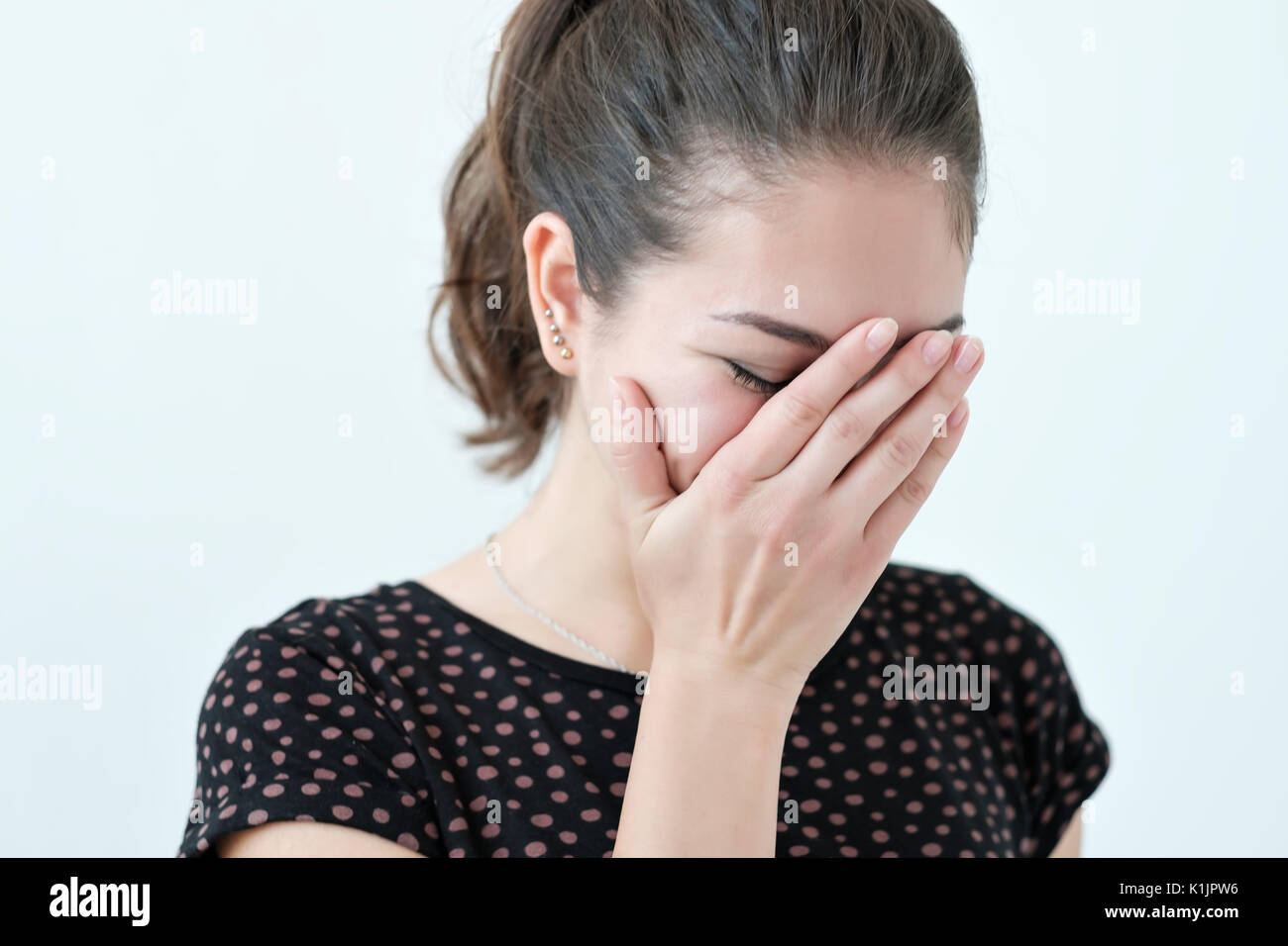 Playful shy woman hiding face with her hands - Stock Image
