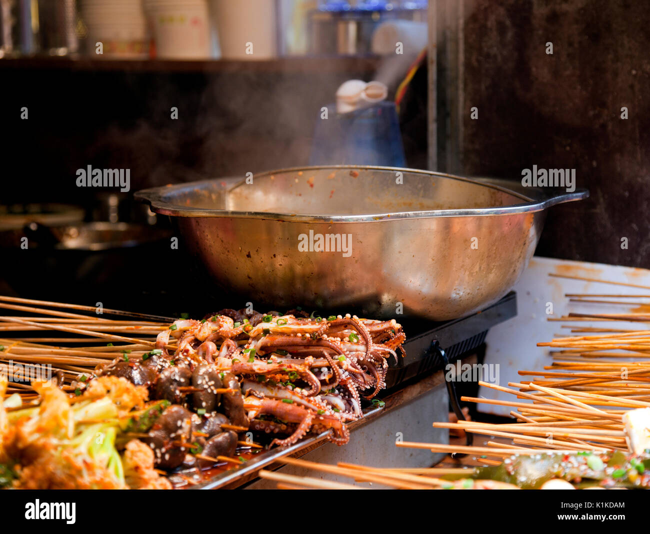 Numerous bits of skewered food, including squid, bugs, tofu, and mystery meat await the steaming wok in this tiny - Stock Image