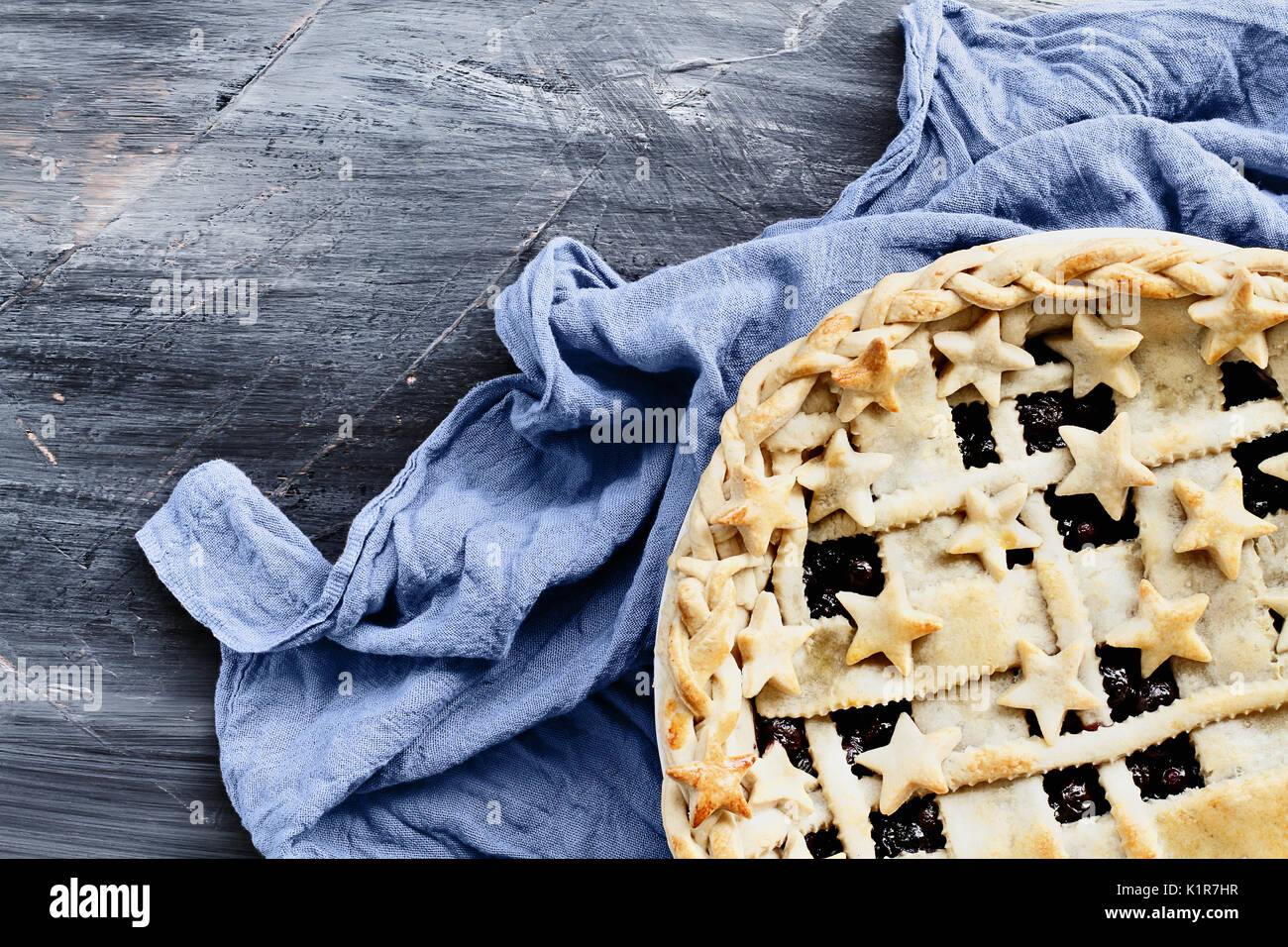 Top view of a blueberry pie with lattice and stars crust with grey napkin over an industrial artistic wooden background. - Stock Image