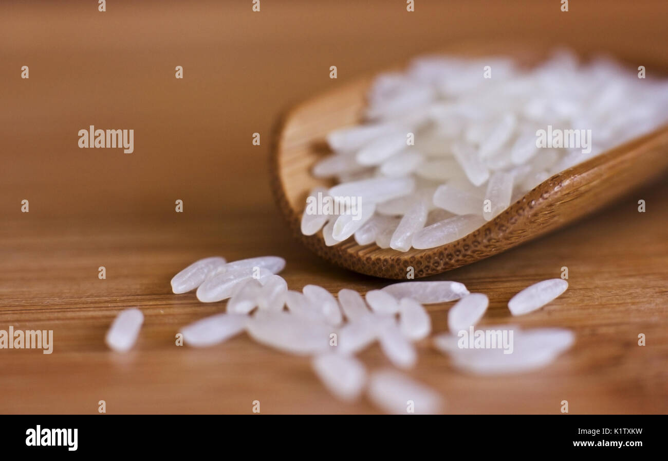 White rice in a wooden spoon. Macro - Stock Image