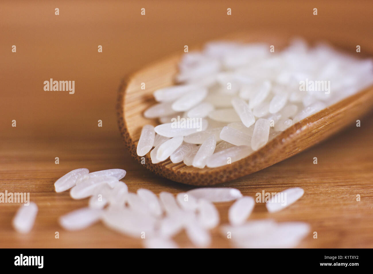 White rice in the wooden spoon. Macro - Stock Image