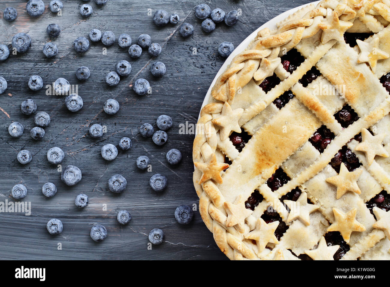 Top view of a blueberry pie with lattice and stars crust and fresh berries scattered across a painted textured wooden - Stock Image