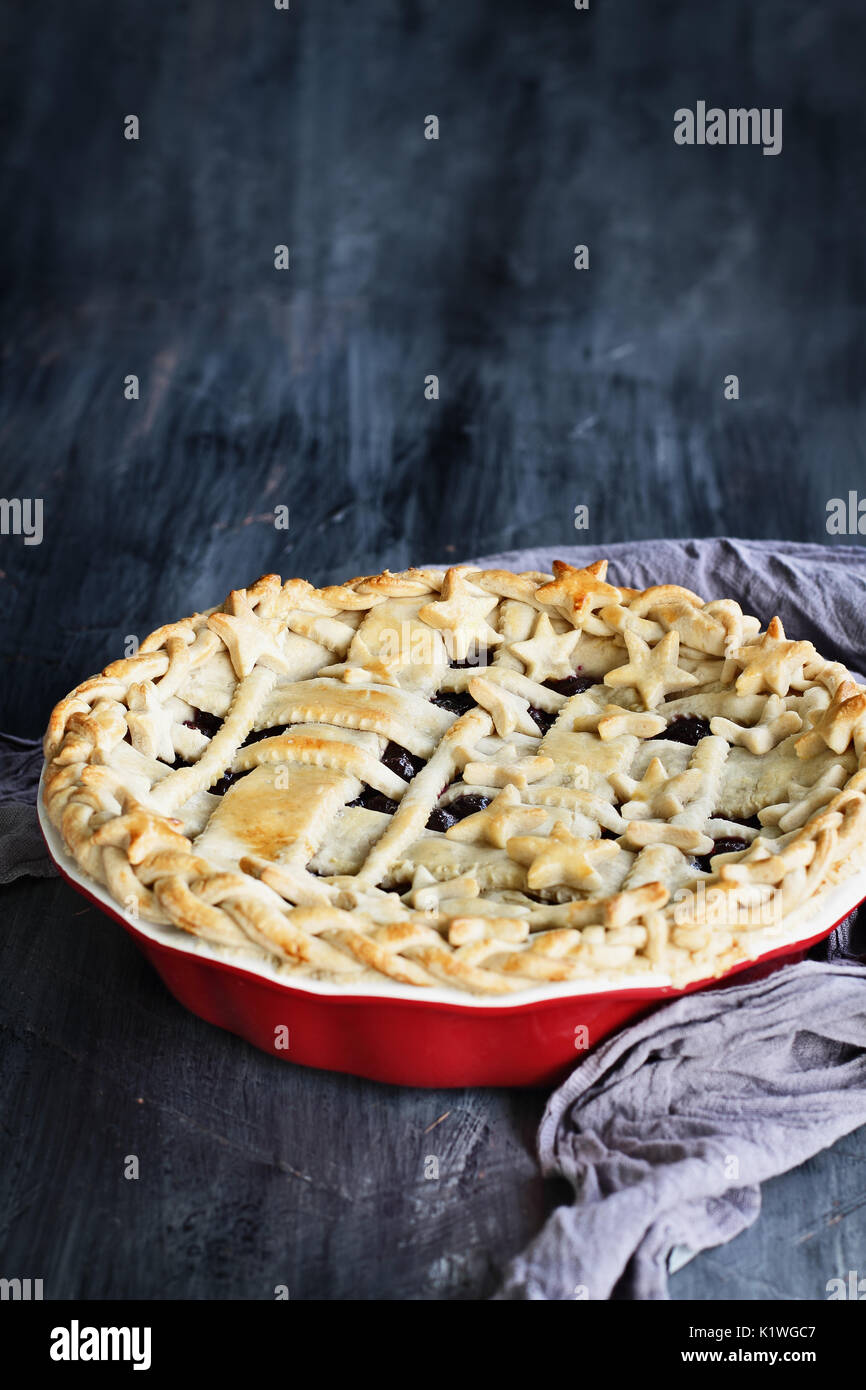 Sweet blueberry pie with lattice and stars crust in a red pie plate against a rustic wooden background. - Stock Image