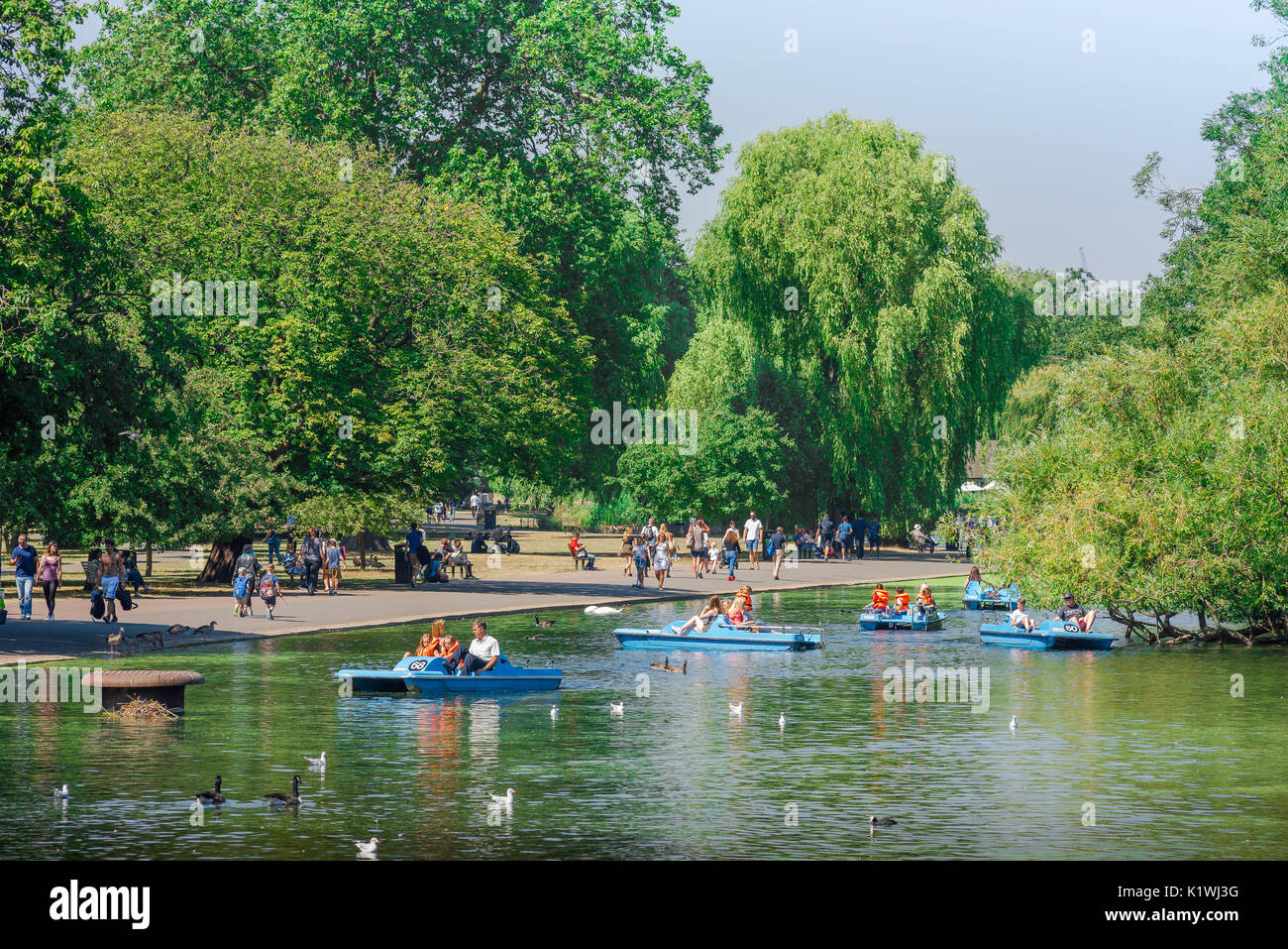 Boating lake London, tourists in pedalos enjoy a summer afternoon on the lake in Regent's Park, London, UK. - Stock Image