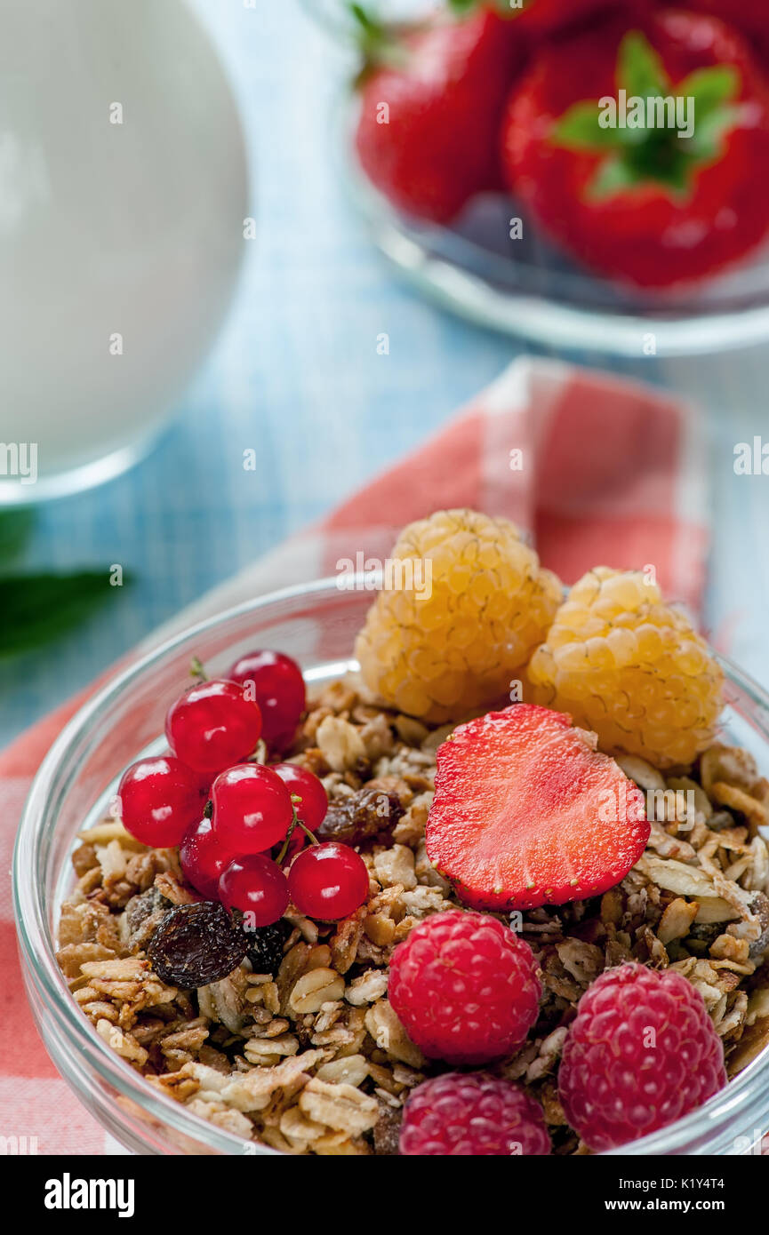 Healthy Breakfast cereals muesli with fruits and berries strawberries, raspberries and red currants with dairy products. - Stock Image