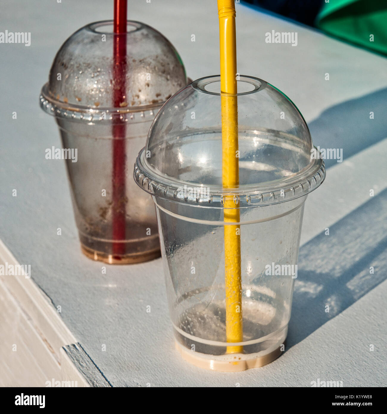 Empty plastic glasses with red and yellow straws stand on a white deck. Some green cloth and reflection of blue - Stock Image