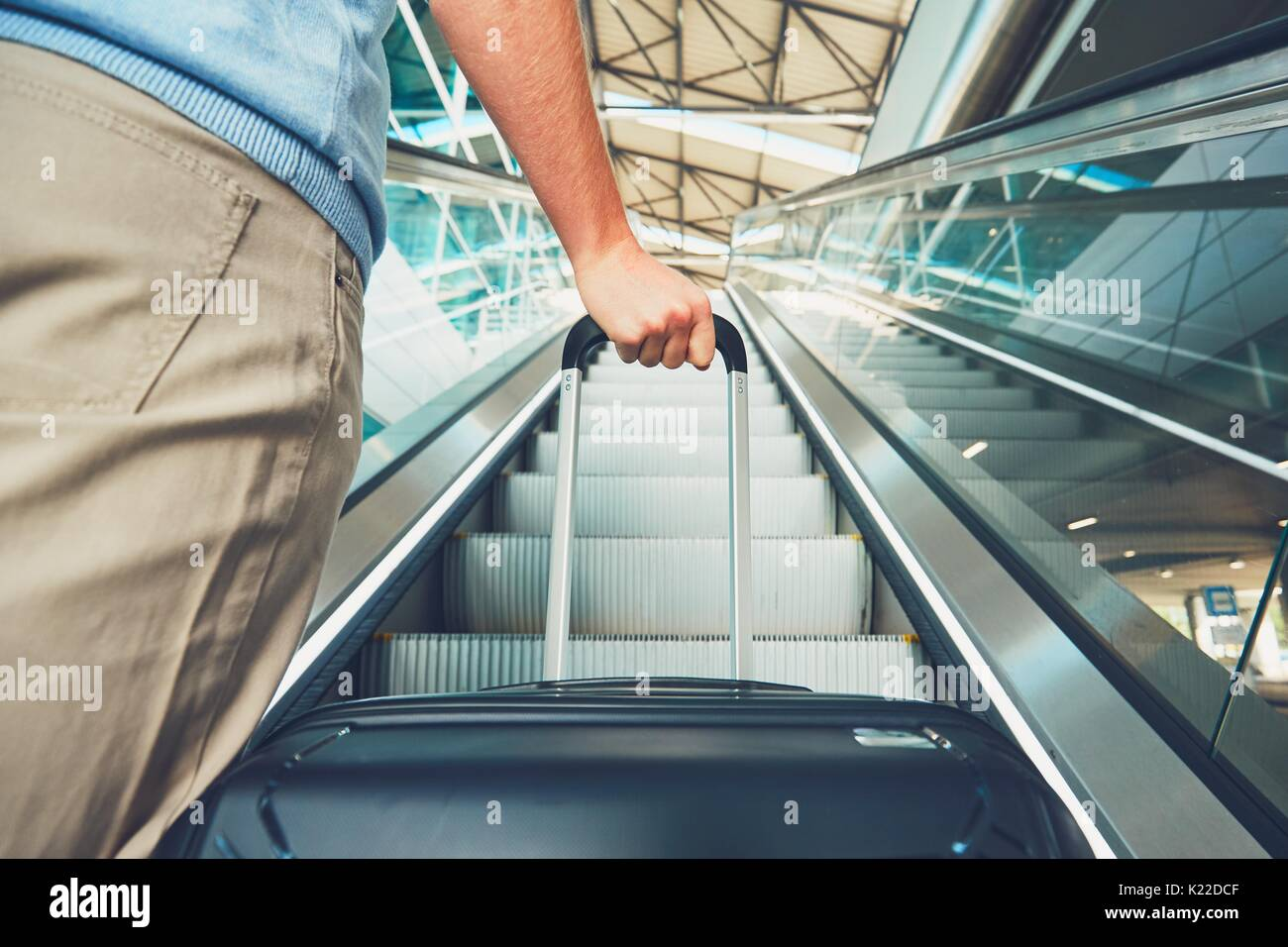 Man traveling by airplane. Hand of the passenger with luggage on the escalator at the airport. - Stock Image