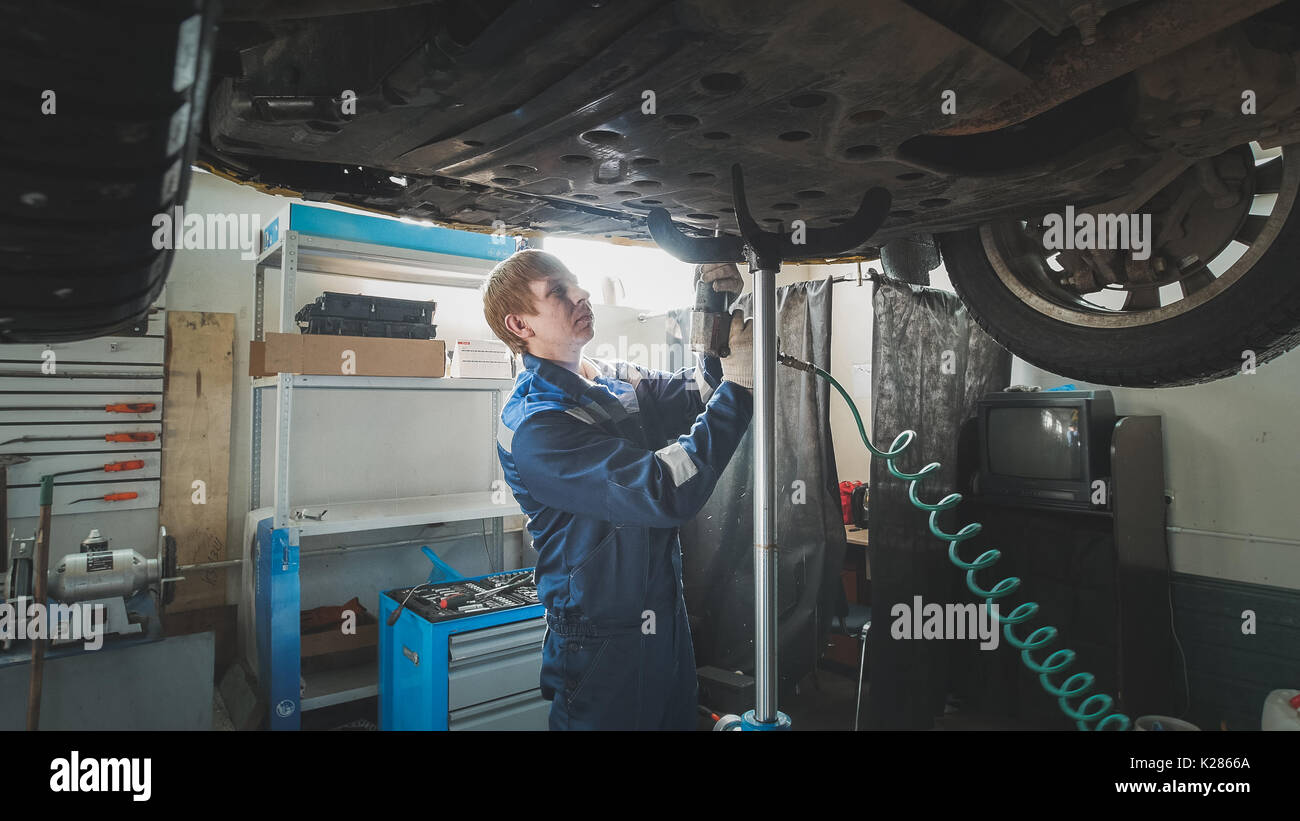 Worker Mechanic unscrewing parts of automobile's bottom under lifted car - Stock Image
