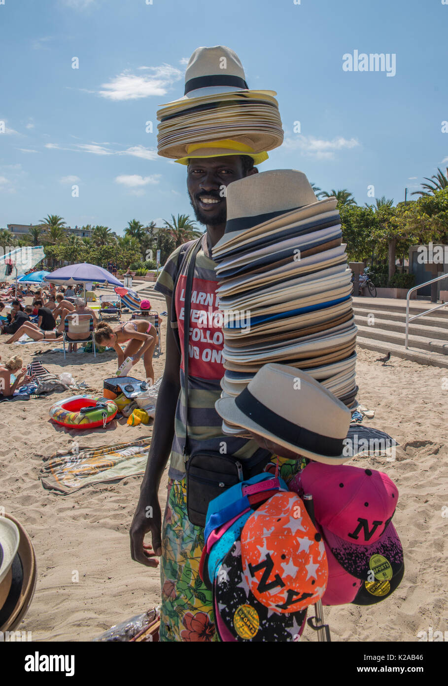 An African man sells straw hats on the beach in Antibes, France Stock Photo