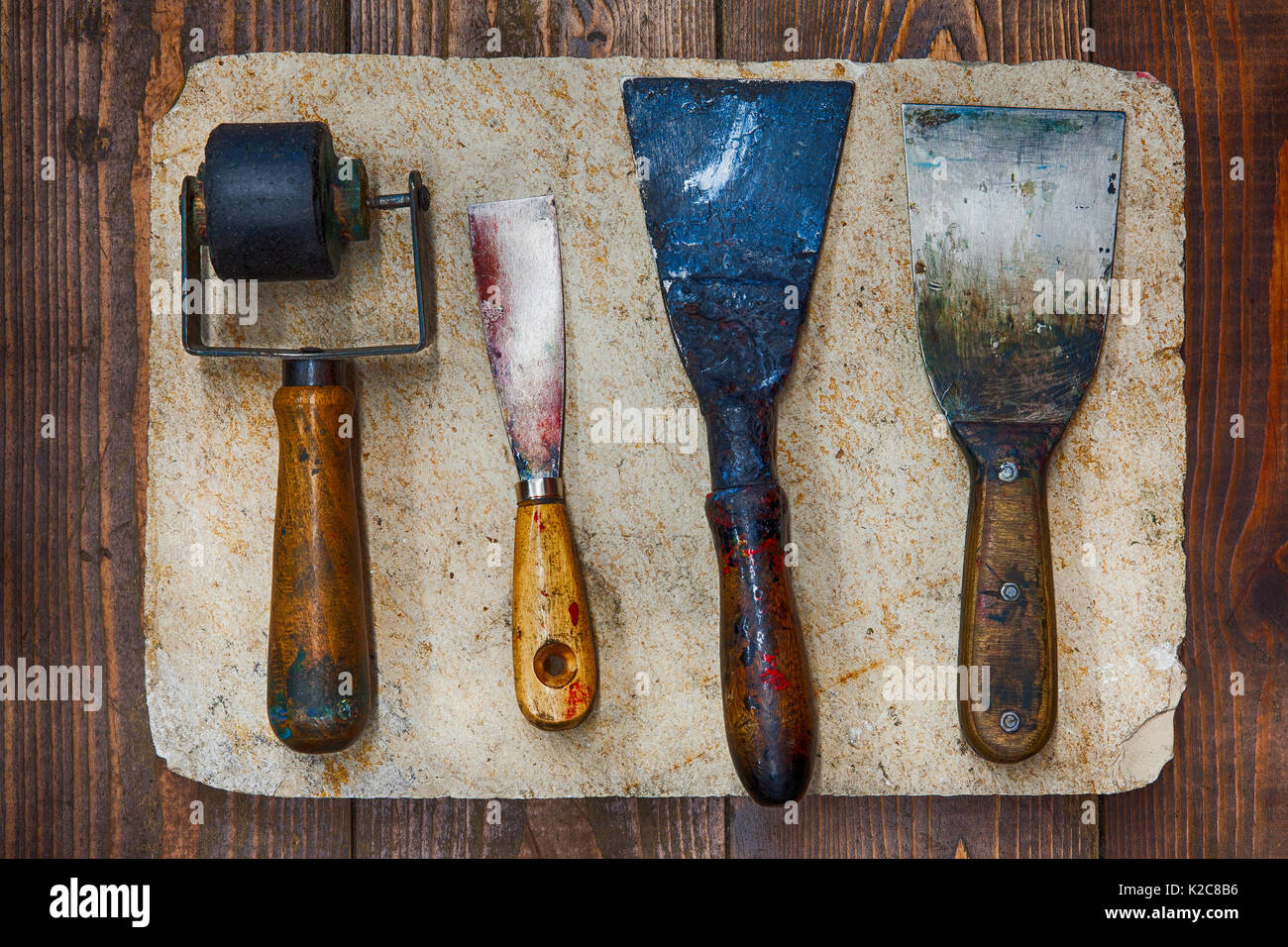 Retro design tools for artist workshop: rubber roller, different size putty knives on stone plate and wooden background. - Stock Image