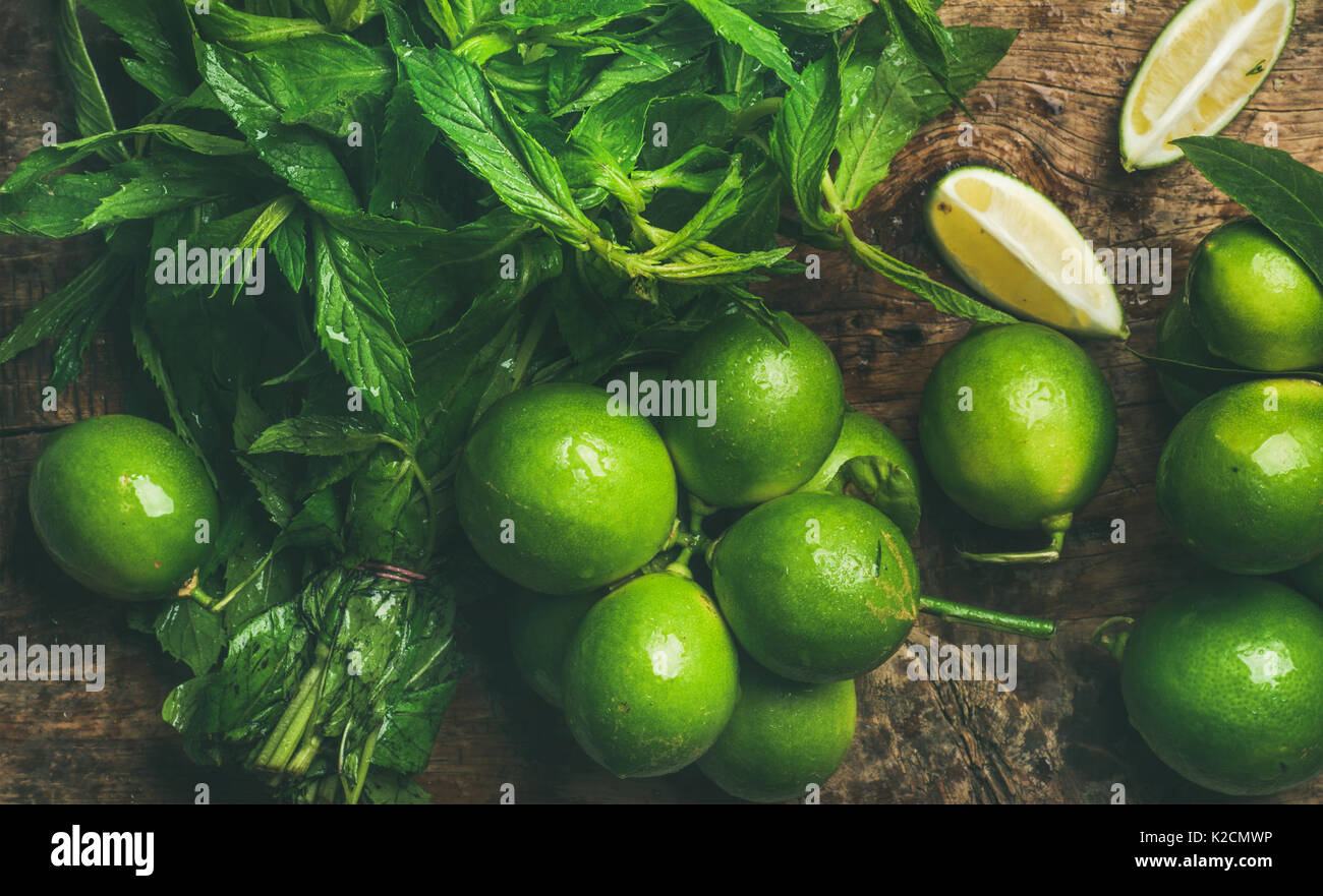 Flatlay of fresh limes and mint for making summer drinks - Stock Image