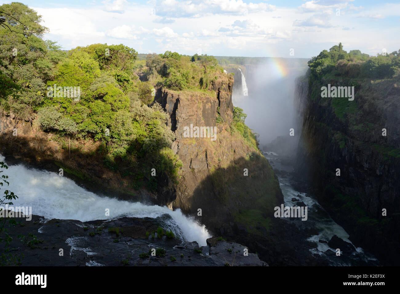 Victoria Falls with mist and rainbow, Zambezi River, Zimbabwe - Stock Image
